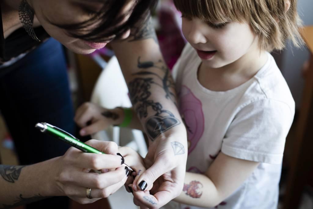 Vaasan: Lapsiperheen ruokapöydässä. Hämeenlinnassa Silavuorten perheessä. Kuvassa Nina tekee leikkitatuointia Niilolle.
